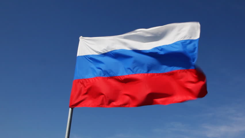 big Russian tricolor flag flutters in wind against blue sky
